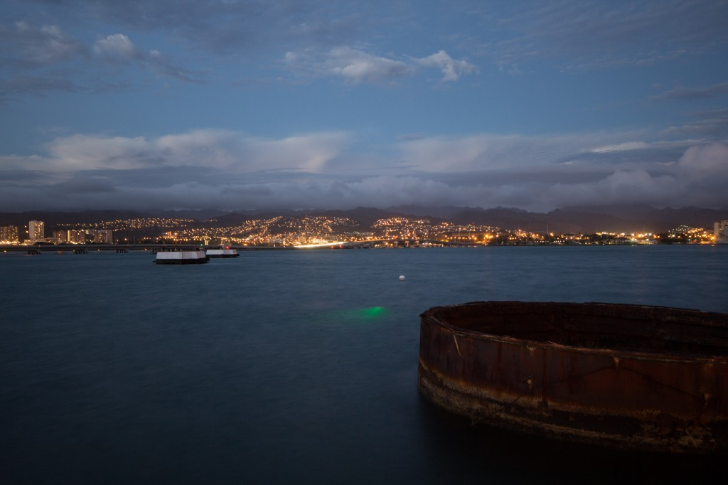 A view of Pearl Harbor, with the top of the USS Arizona in the foreground, and the green light of the underwater laser scanner glowing in the water.