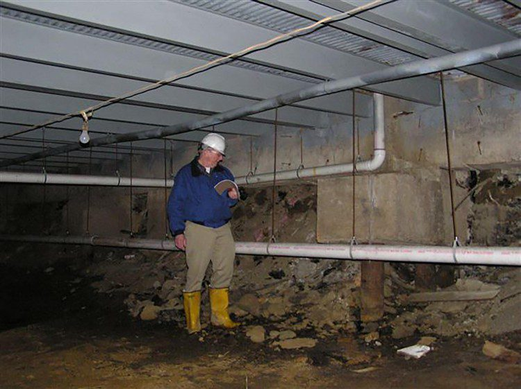 "An inspector is shown in the ""crawl space"" of the prior mall, where grade level is estimated to have settled about five feet since original construction in 1964.  CREDIT: AET Inc."